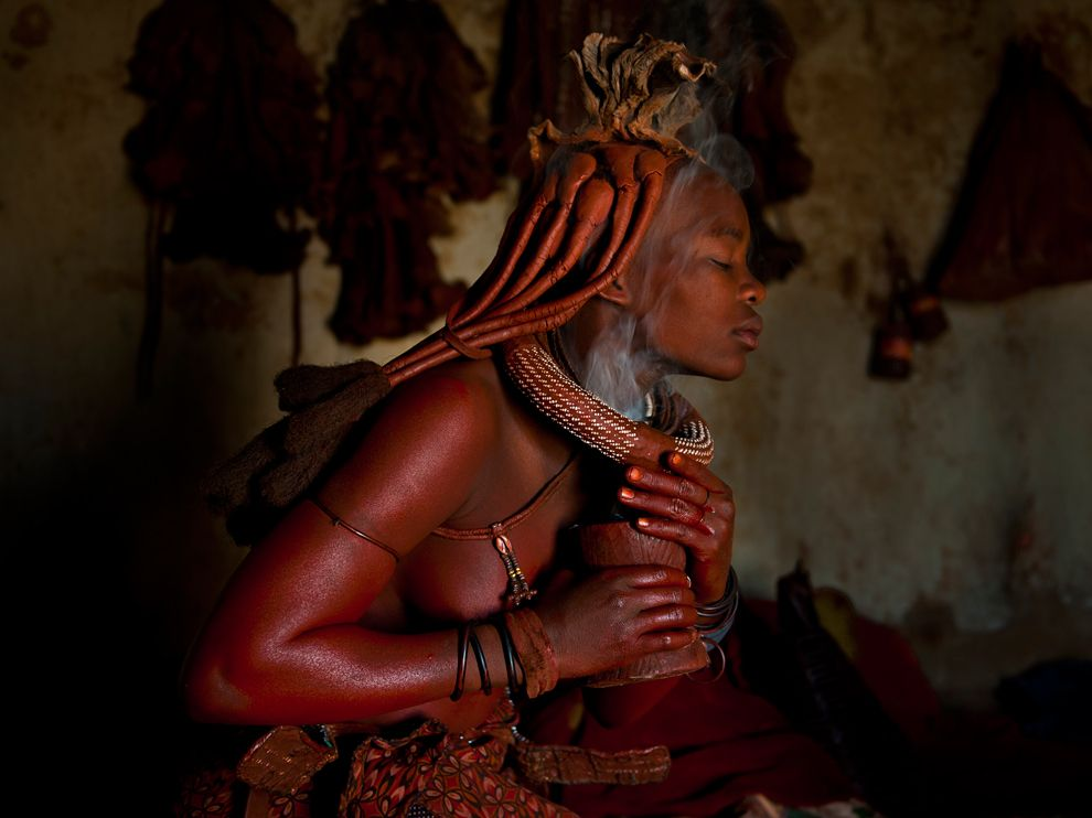 Himba woman burning aromatic herbs for a perfumed smoke bath. - Photograph by Dominique Brand